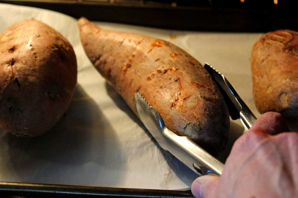 turning sweet potato over with tongs