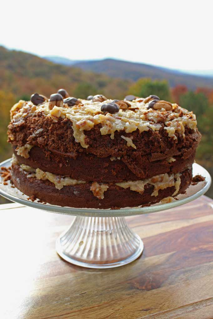 This German chocolate cake is a deliciously rich dark and extra chocolaty cake with layers of caramelized gooey coconut-pecan frosting with toasted pecans. #germanchocolate #cake #baking #coconut #pecan #frosting #dessert #recipe