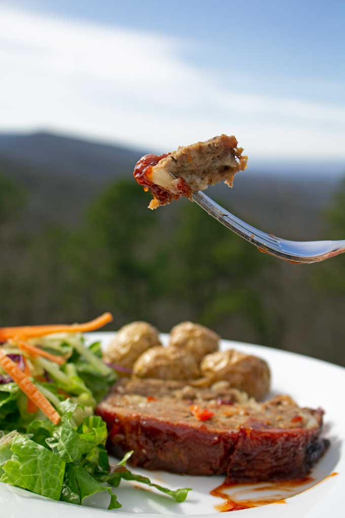 Meatloaf on fork with plate and mountain view