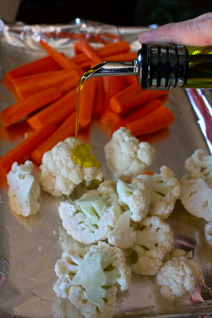 pouring oil over carrots and cauliflower