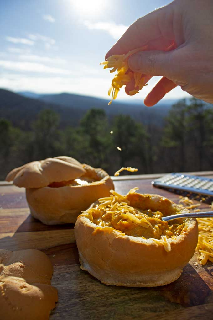 sprinkling cheese into soup in bread bowl with mountain view