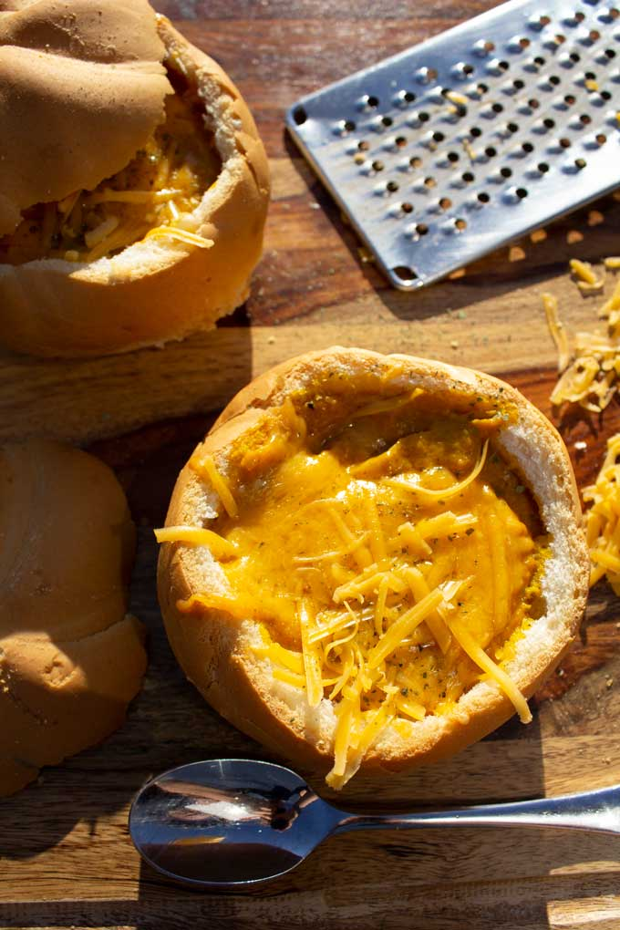 Sweet savory carrots, creamy cauliflower, and salty sharp cheddar cheese come together as the base of this vegetarian carrot-cheddar soup in bread bowls.