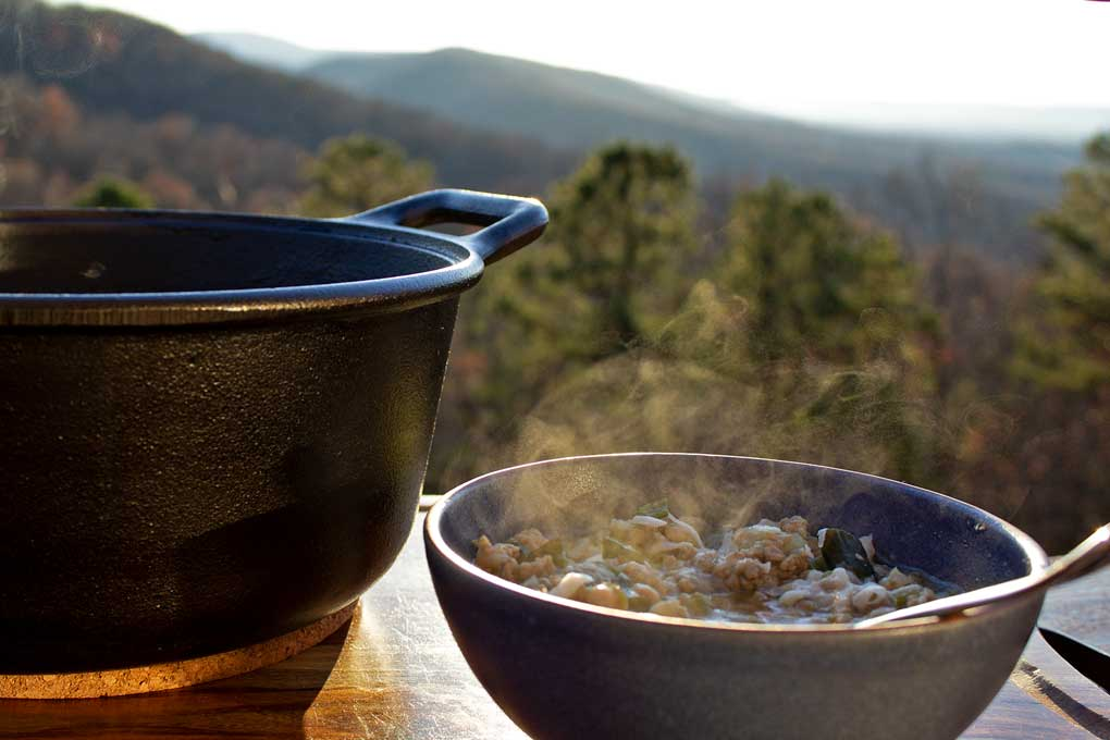 pot of white bean and pork chili with steaming bowl and mountain view