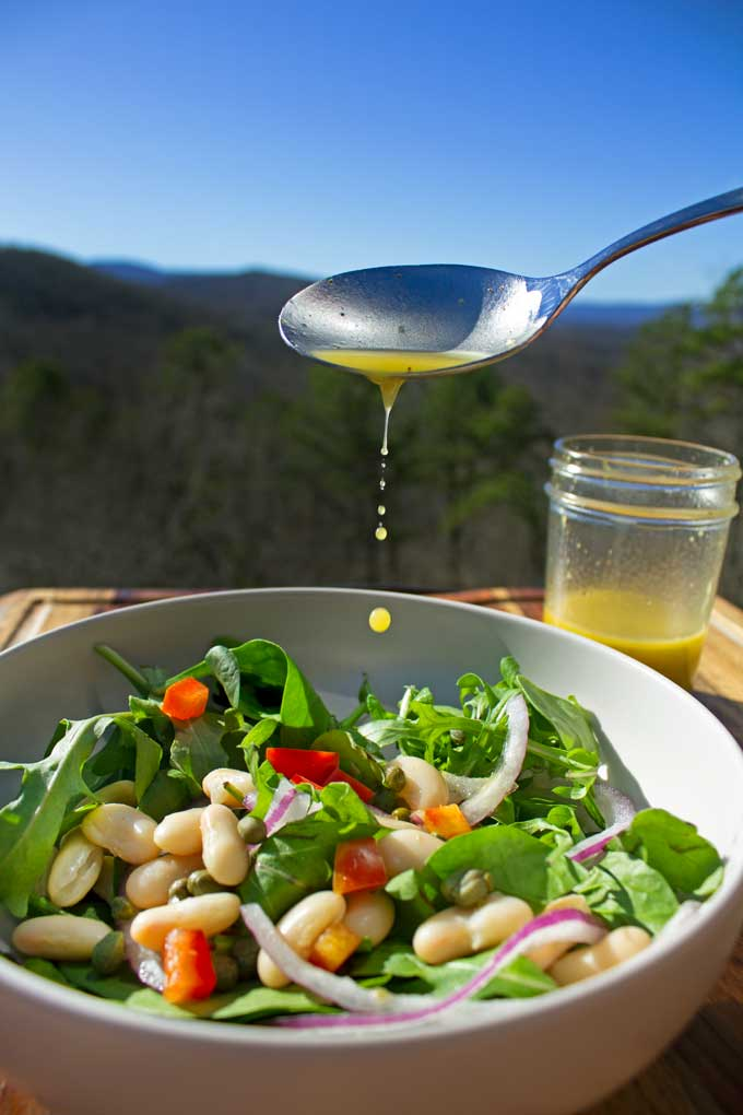 drizzling dressing onto salad with mountain view