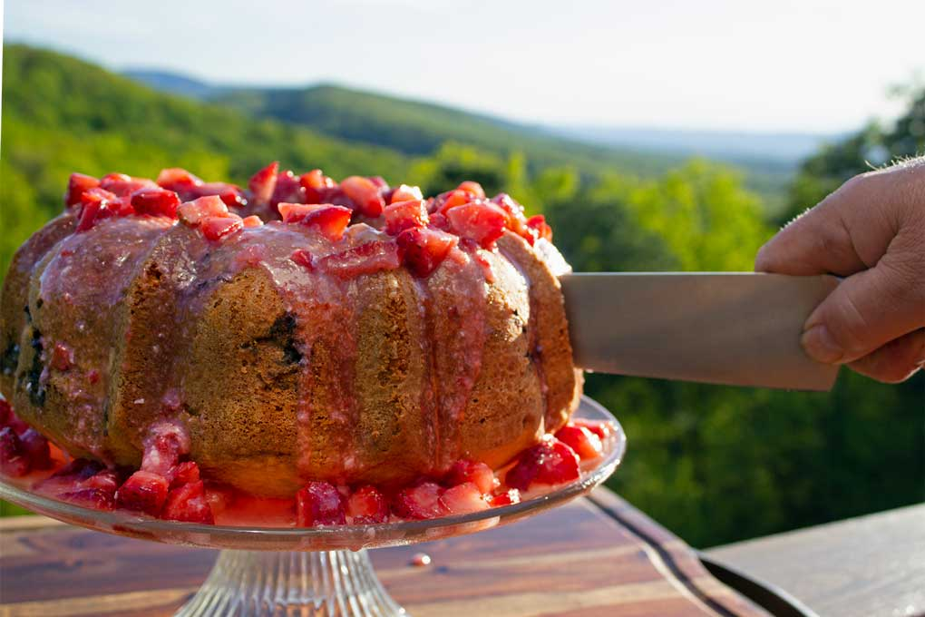 cutting strawberry bundt cake with mountain view