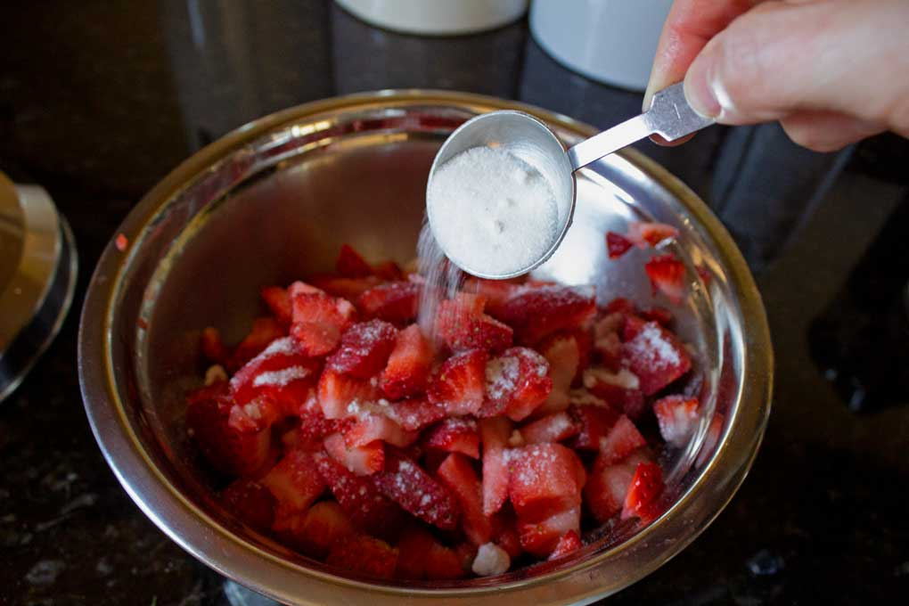 adding sugar to strawberries