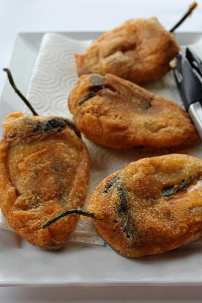 draining authentic chile rellenos on platter
