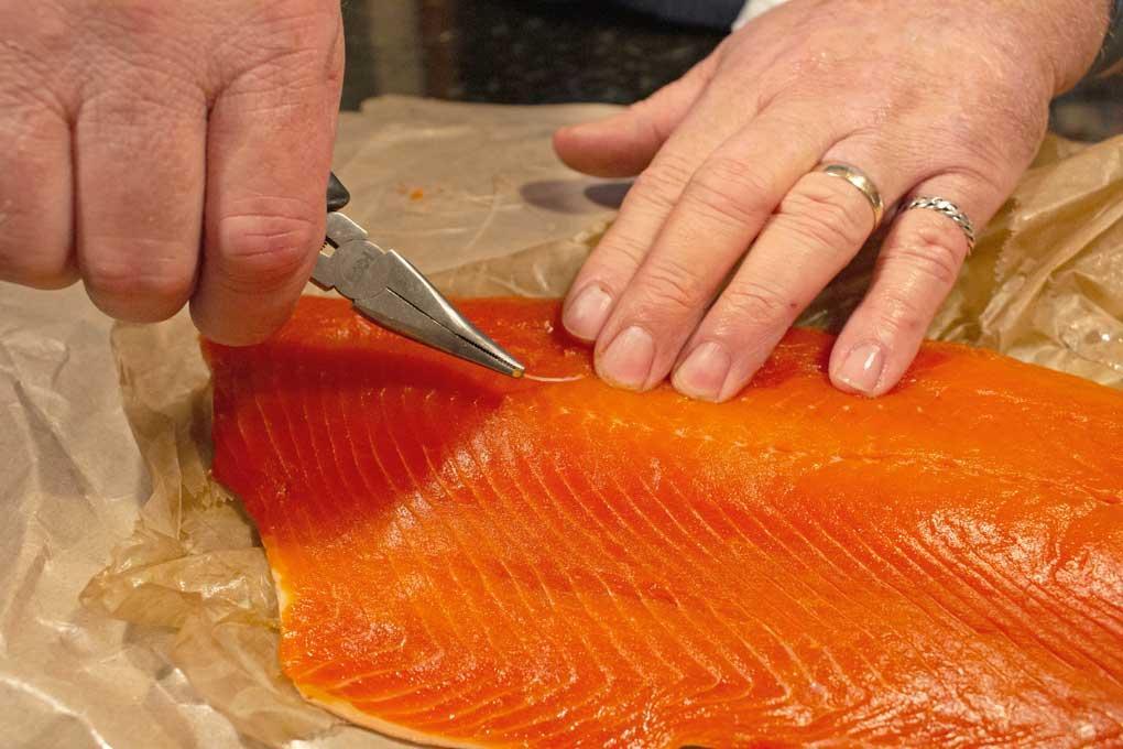 pulling bones from salmon fillet