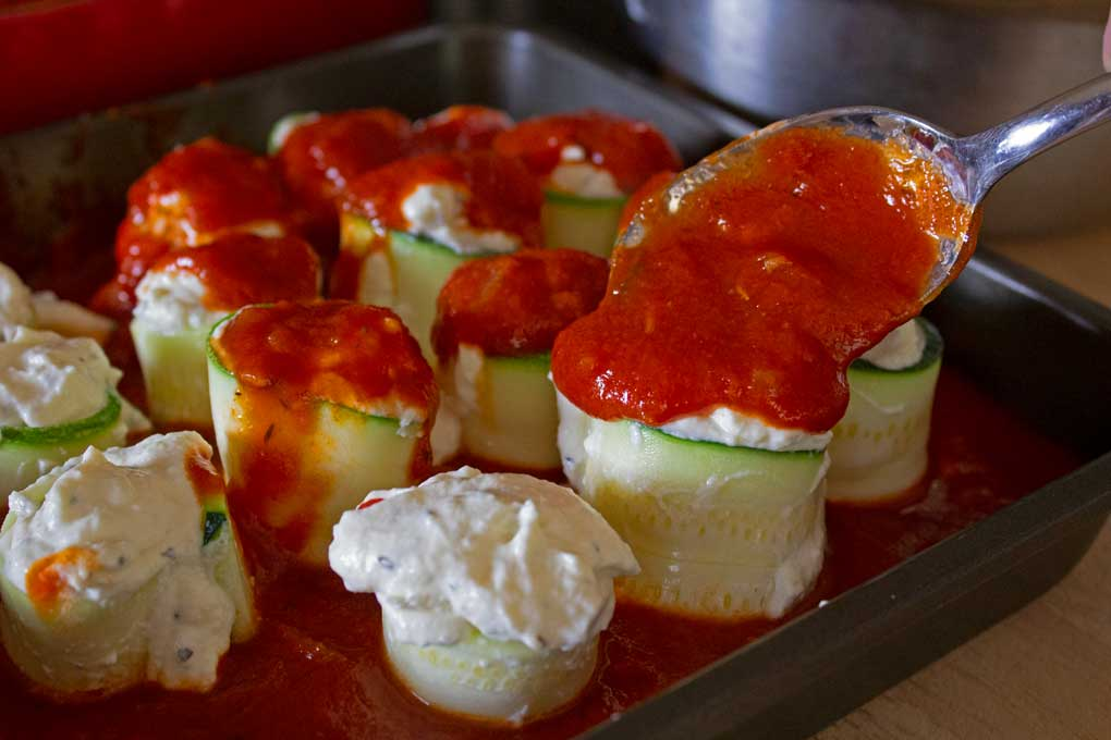 topping the zucchini rolls with sauce
