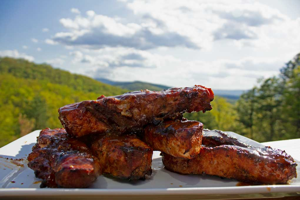 grilled country-style pork ribs on platter with mountain view