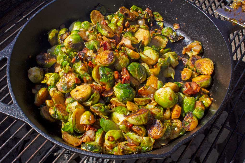 grilled brussels sprouts with bacon and barbecue sauce in pan on grill