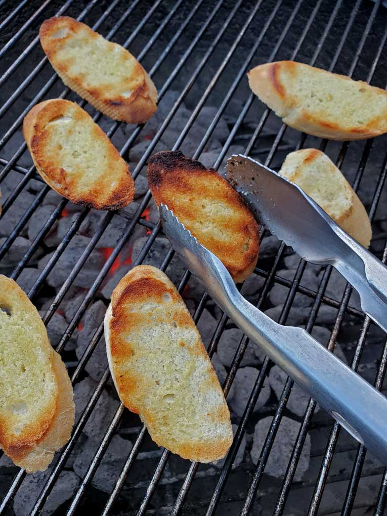 tossing grilled toast with tongs for grilled tomato soup