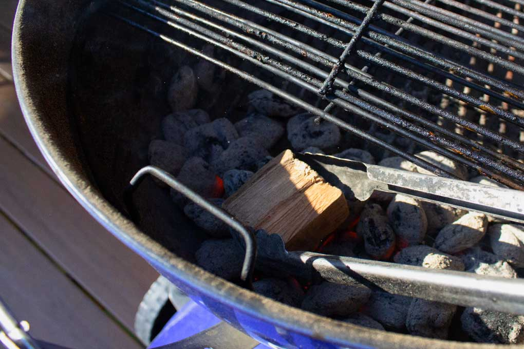 placing wood chunk in charcoal basket
