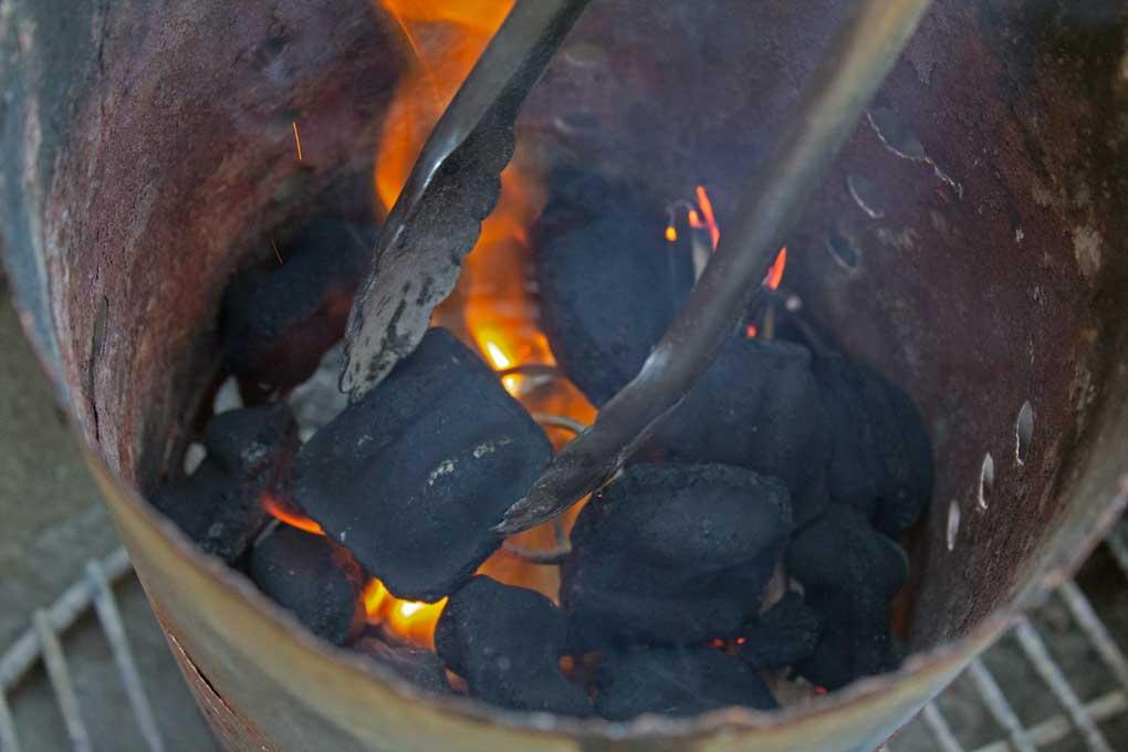 lit charcoal inside charcoal chimney