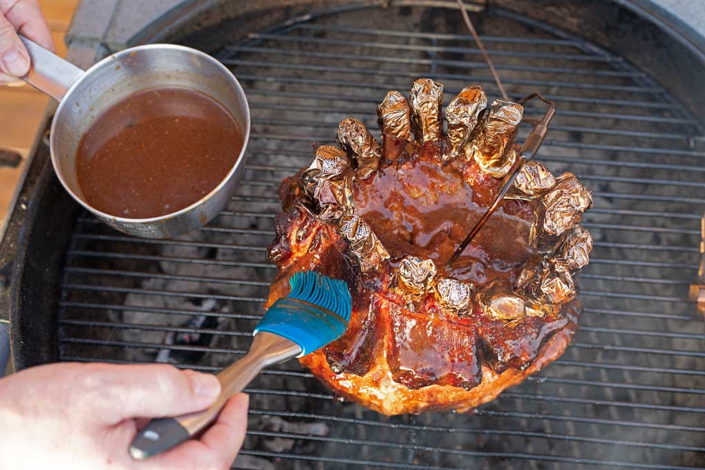 brushing the smoked pork crown roast with bbq sauce