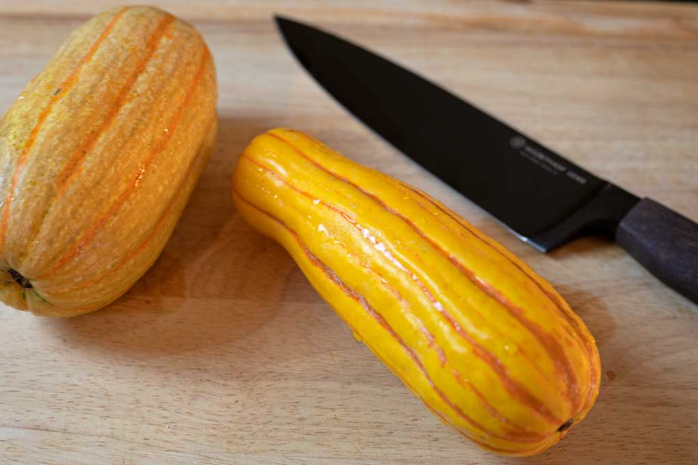 delicata squash on cutting board with knife