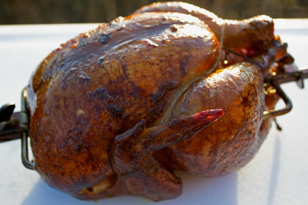 rotisserie-smoked chicken resting on carving board