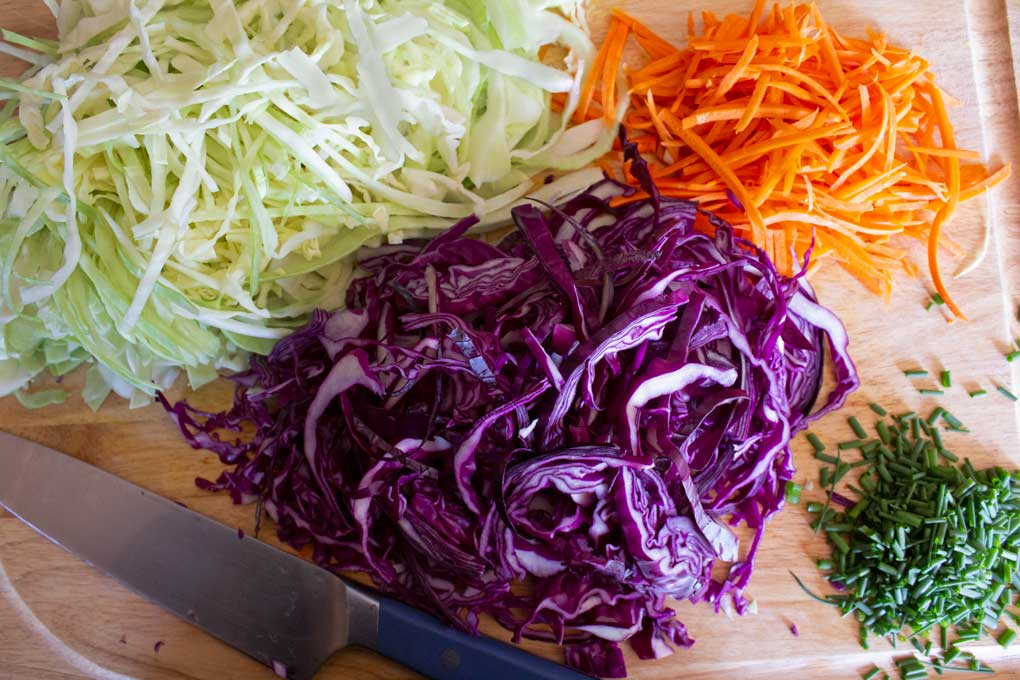 chopped cabbage carrots and chives on cutting board with knife
