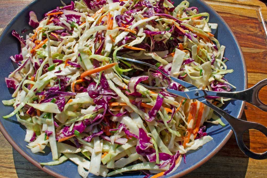 easy coleslaw in bowl with tongs