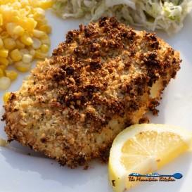 prepared air fryer cod on plate with lemon wedge, corn and slaw