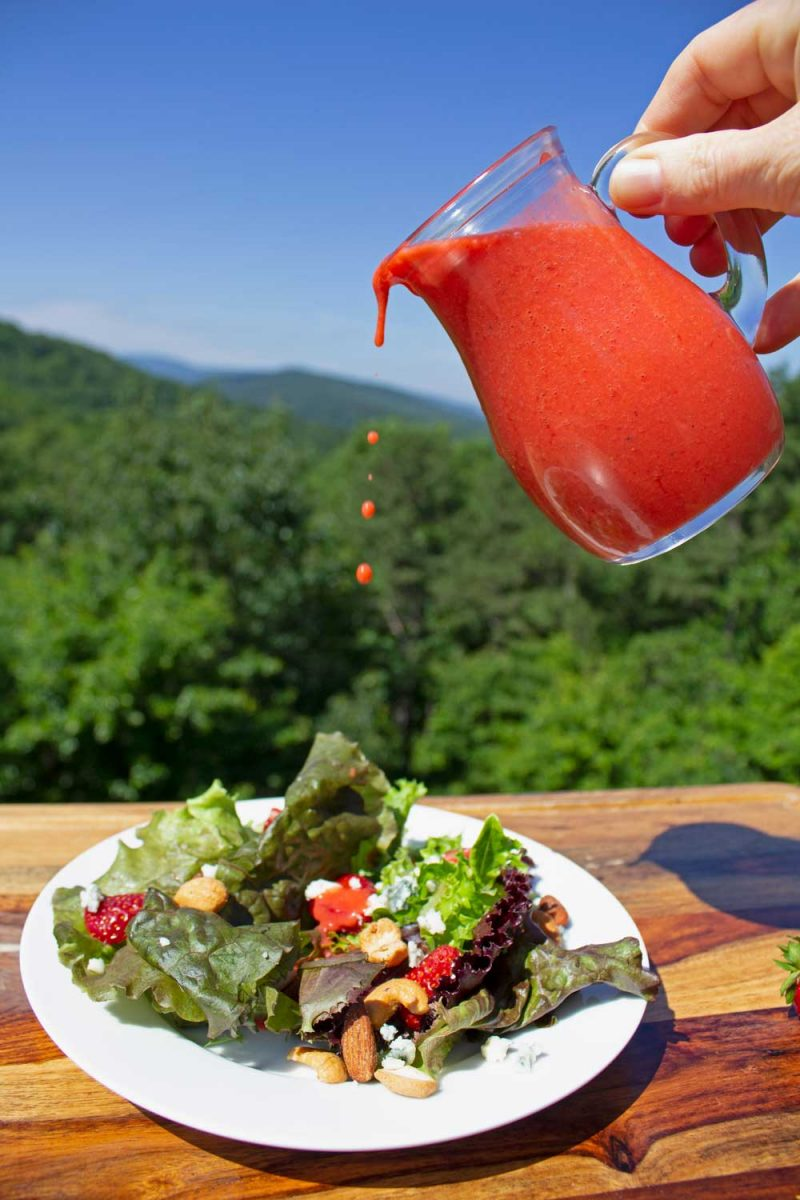 pouring dressing over salad with mountain view