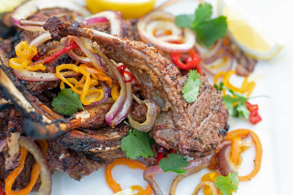 tandoori lamb chop on platter with onions, peppers, lemon wedges and cilantro