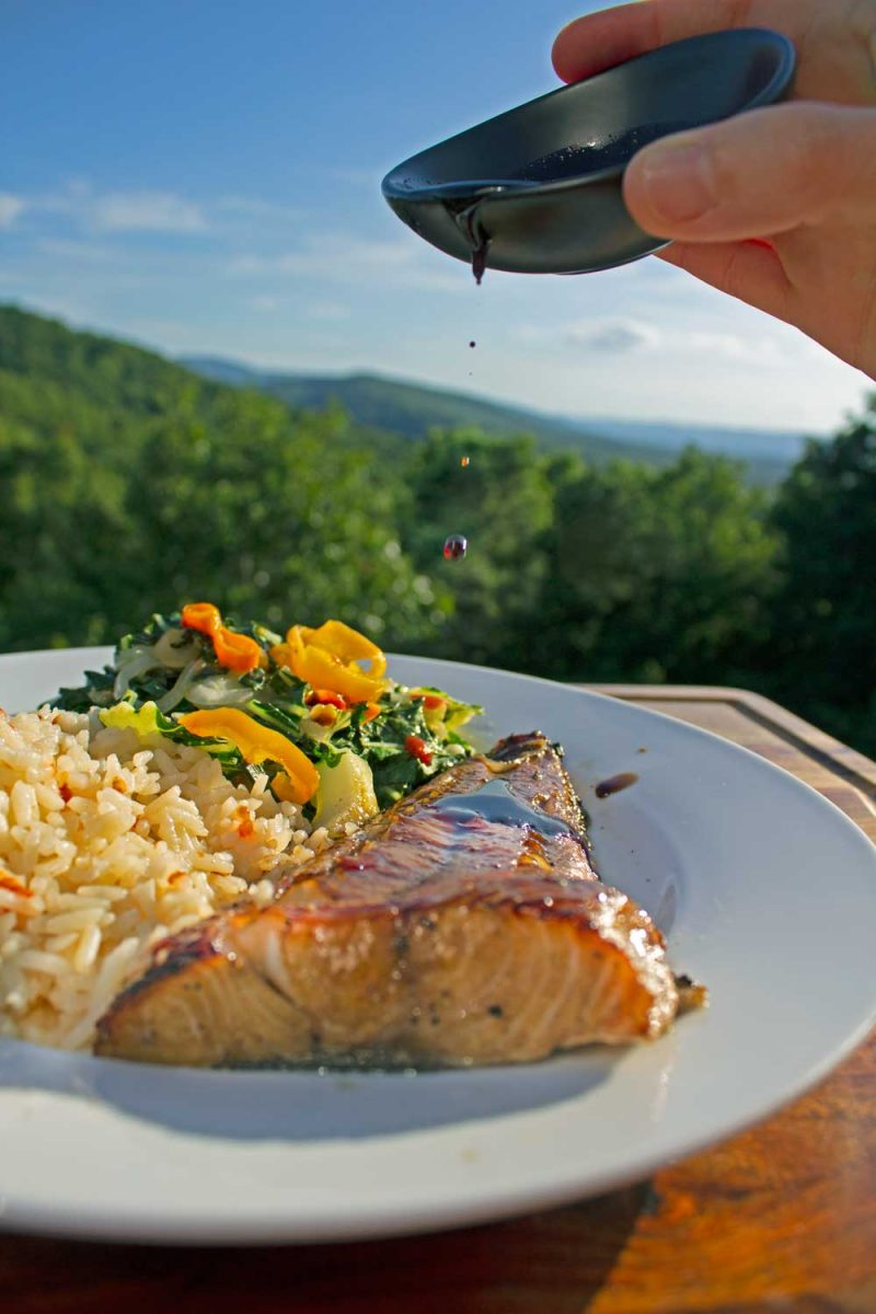 drizzling soy glaze onto plate of cod with mountain view