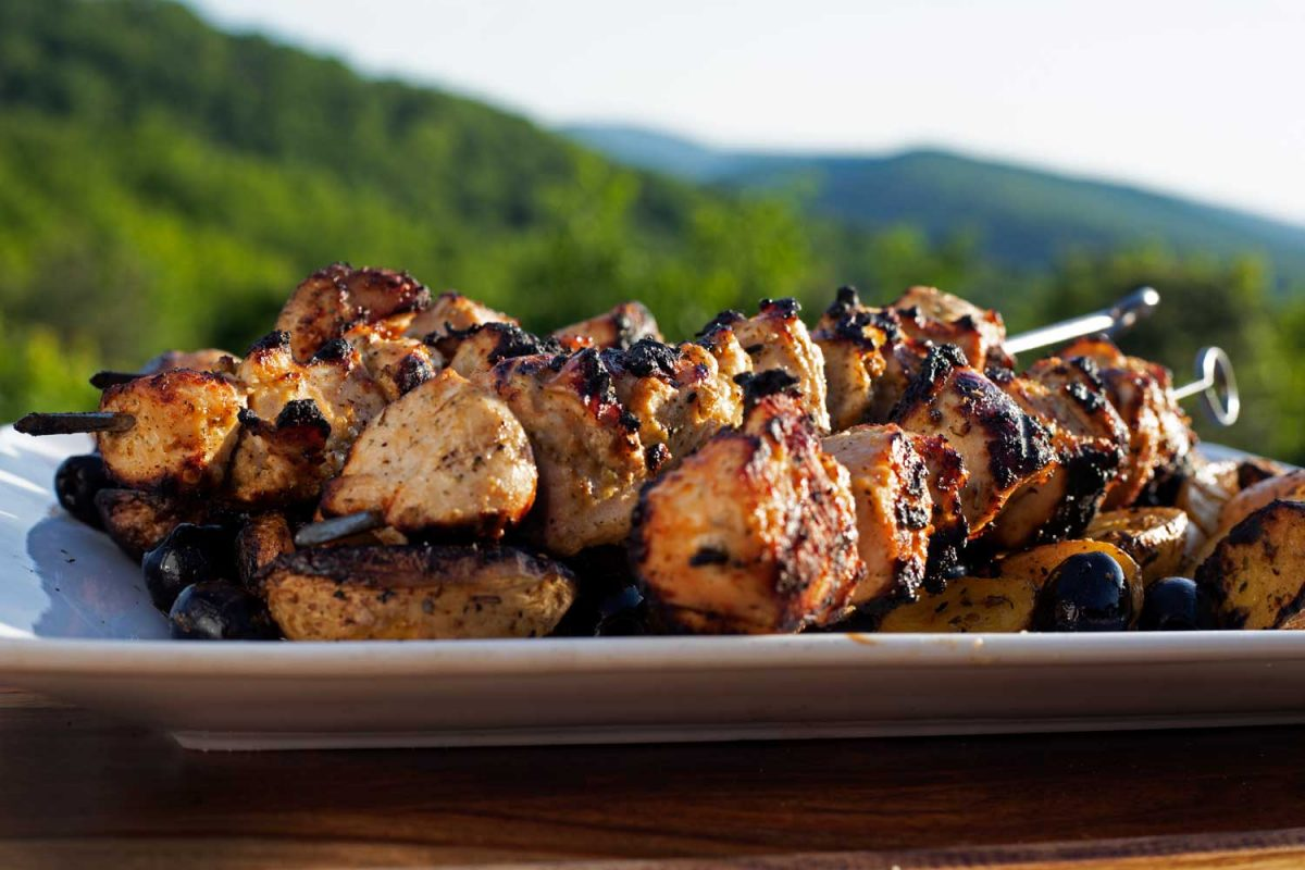 Greek chicken kabobs on platter with mountain view