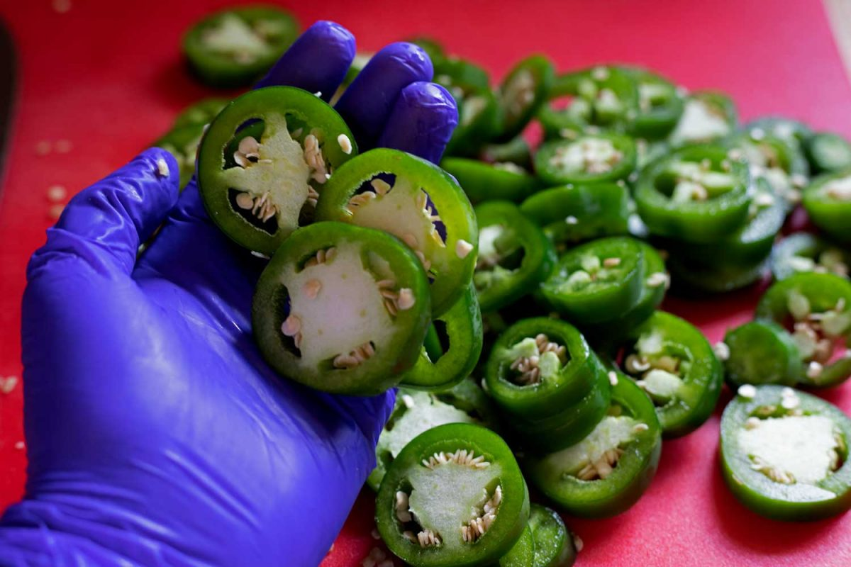 gloved hand with jalapeno slices