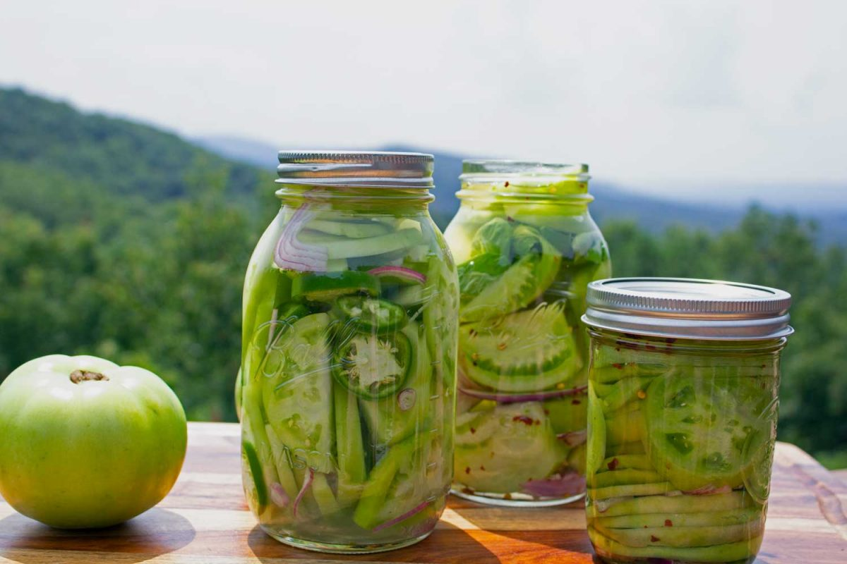 jars of pickled green tomatoes with mountain view