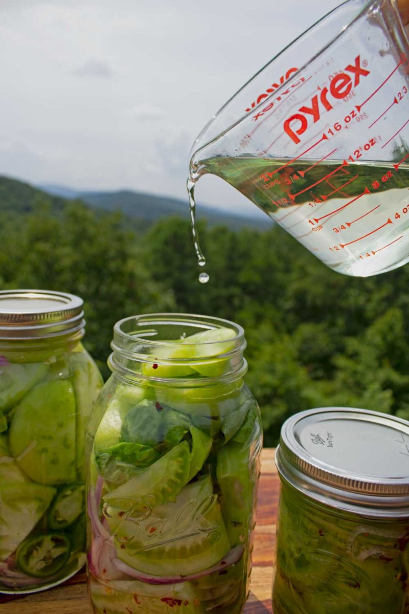 pouring brine into jar of green tomatoes