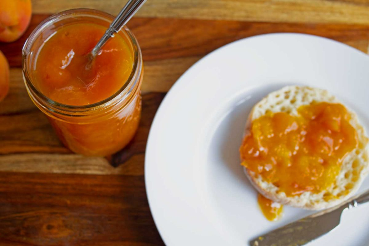 jar of apricot jam with toast on plate