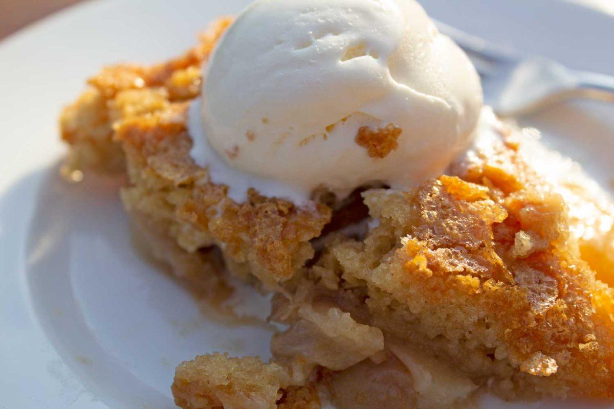 peach skillet cake with scoop of melting vanilla ice cream