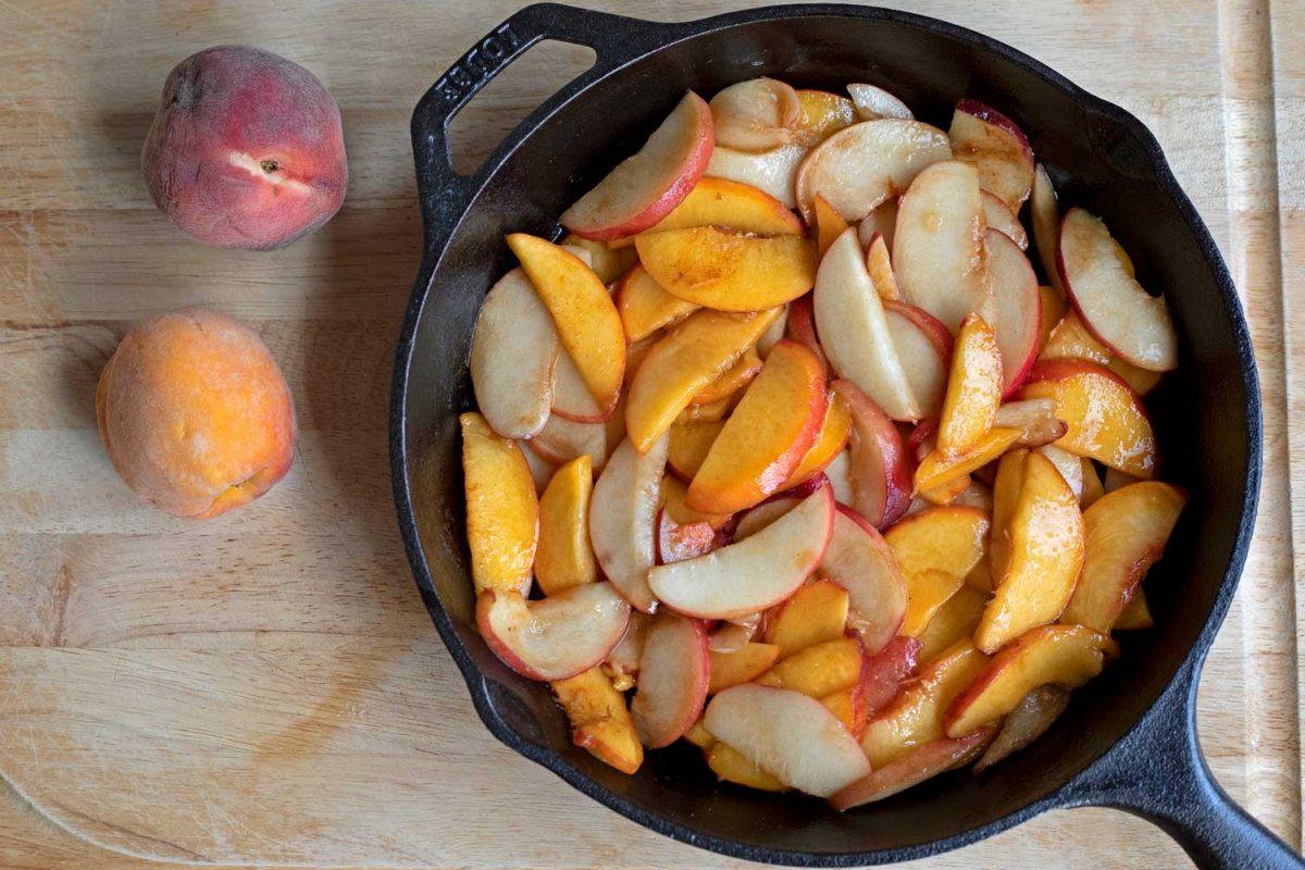 peach slices inside cast-iron skillet