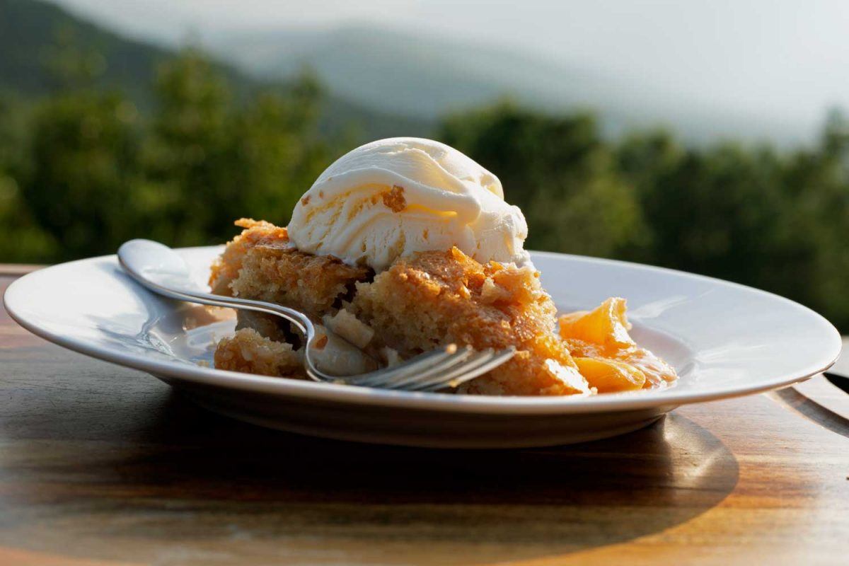 slice of peach skillet cake topped with ice cream with mountain view