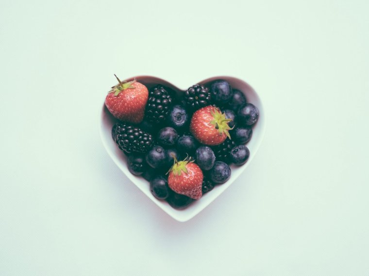 bowl of blueberries and strawberries in a love heart shaped bowl on a blue plain background