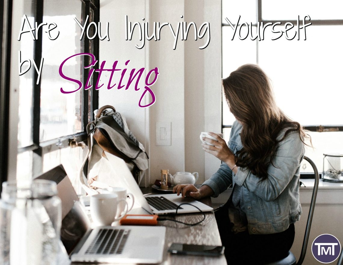 woman sitting at a desk holding coffee looking at computer with text overlay - are you injuring yourself by sitting feature