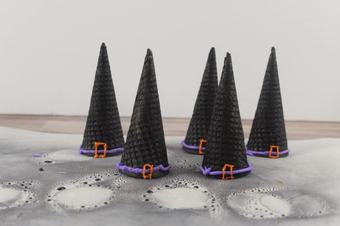 witch cones with piped icing on parchment paper