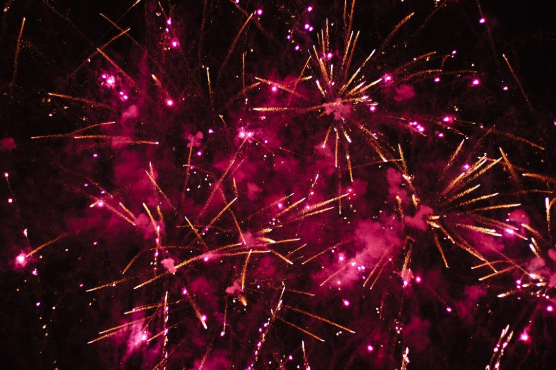 pink and red fireworks all over a black background with gold specks