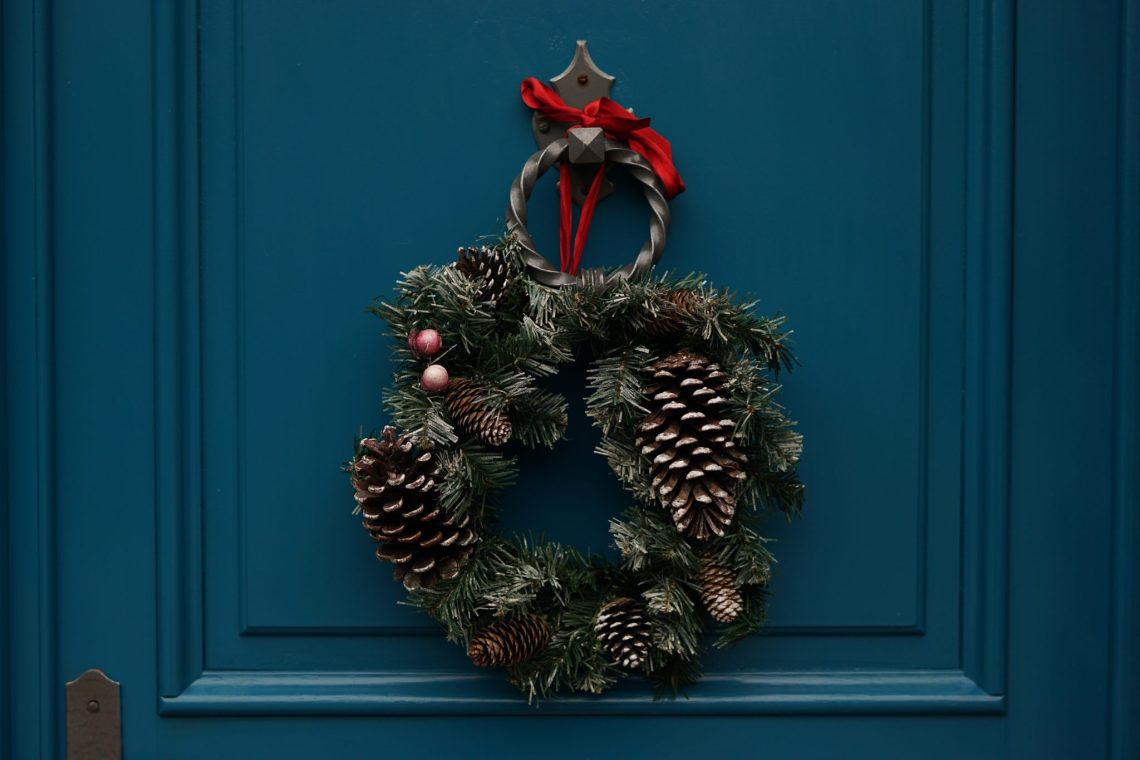 close-up of a green Christmas wreath on a blue door