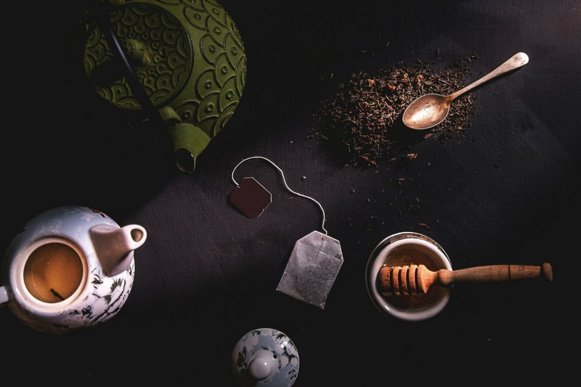 tea bag, honey stick and spoon on a darkened table to beat new year bloating