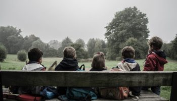 groups of kids facing away from the camera sitting on a bench at the park on a grey day.