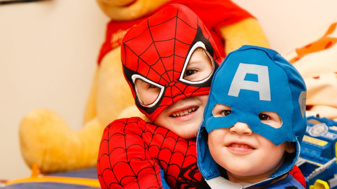 two kids in spiderman and captain america costume smiling