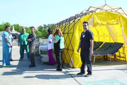 Personnel from different agencies in Whitfield County, Ga., and its municipalities stand ready to utilize a decontamination tent for those affected by hazardous materials during a fullscale disaster preparedness exercise in 2015. (Photo provided)