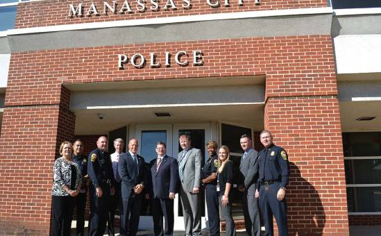 Officials from Manassas, Va., including Police Chief Doug Keen — third from left in uniform; Mayor Harry J. Parrish II — next to Keen in the white shirt; and City Manager W. Patrick Pate — middle with glasses — gathered recently with members of the Commission on Accreditation for Law Enforcement Agencies and police personnel in front of the Manassas Police Department. (Photo provided)