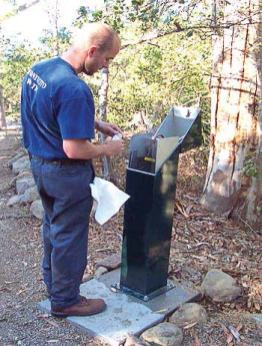 A technician draws a water sample from a water sampling station; water sampling stations reduce chances of receiving a false positive when testing water. (Photo provided)