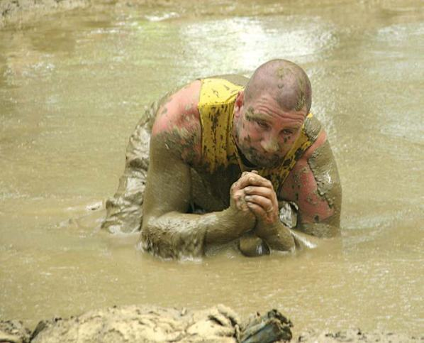 A competitor emerges from the muck after trying for a save during the Hog Wallow Mud Volleyball Classic, a Hog Days festival staple since 1983. (Photo provided by Larry Flannery)