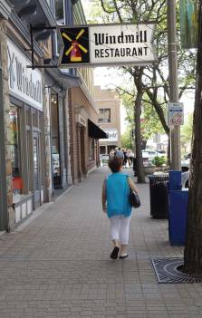 A visitor to downtown Holland, Mich., strolls down a sidewalk along Eighth Street, one of the first sections of heated sidewalks. (Photo by Denise Fedorow)