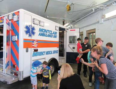 Montclair, N.J., EMT Jason Batruk — in the navy T-shirt and holding a child — is shown giving an ambulance tour to some local children during Montclair's 2016 Walnut Street Fair. The fair is held just a couple of weeks before National EMS Week, so the ambulance service has piggybacked onto that event to do an open house and show equipment to the public. (Photo provided)