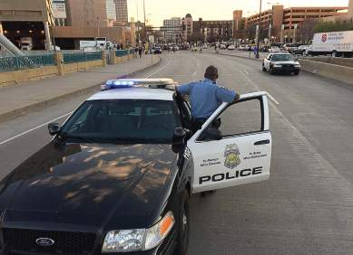 A Minneapolis police officer stands back and observes as a protest takes place in the city. (Photo provided)